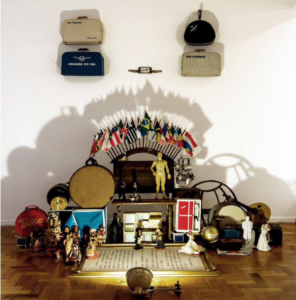 Cosmopolita, 2014 | instalação com carteira escolar, malas, objetos variados, luz e sombra | 260 (L) x 270 (A) x 170 (P)